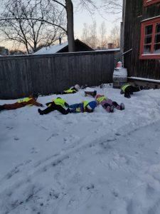 lapset makaavat lumisessa maassa ja katsovat taivaalle.