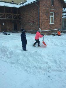 yksi lapsi seisoo lumikasassa, toinen lapsi pitää kädessään lumikolaa.