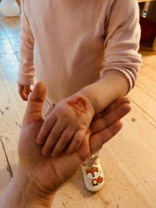 kuvassa lapsen käsi jossa on punainen sydänleima.