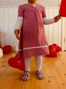 lapsi katsoo käyttäjää ja pitää kädessään punaista ilmapalloa.