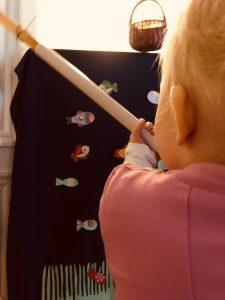 kuvassa lapsi pitää keppiä kädessä ja onkii sermin yli.