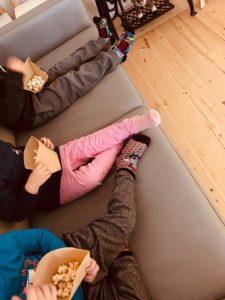 kolme lasta istuu sohvalla popcorneja kädessä.