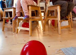 lapsia istuu tuoleilla ringissä.