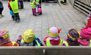 lapset istuvat rivissä penkillä ja katsovat eteenpäin esityksiä.
