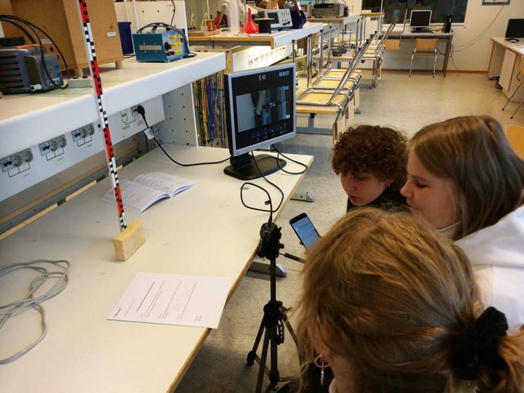 Kolme opiskelijaa tarkastelee taulusienen putoamisesta otettuja kuvia ja tekee laskelmia.