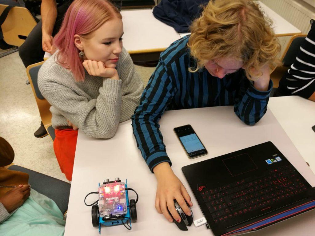 Kaksi opiskelijaa tietokoneen ja pienen automaisen robotin ääressä.