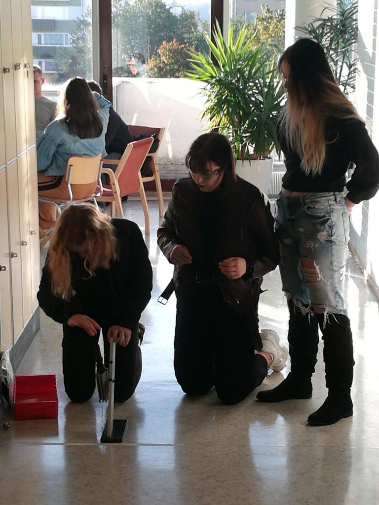 Kolme opiskelijaa virittämässä kuulatykkiä.
