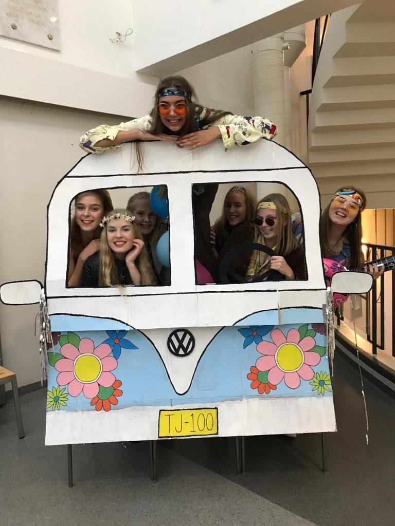 Iloiset abit hippibussissa.