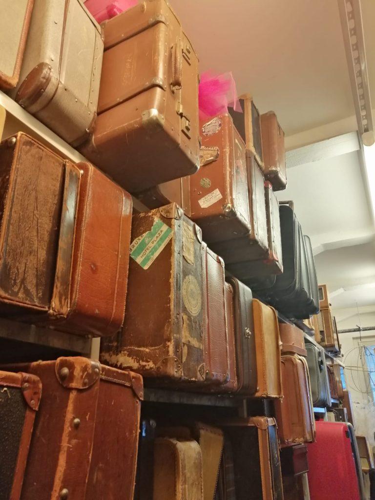 Erilaisia matkalaukkuja hyllyssä.