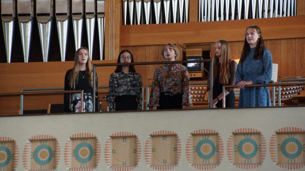 Viiden hengen lauluyhtye esiintyy kirkon parvella.
