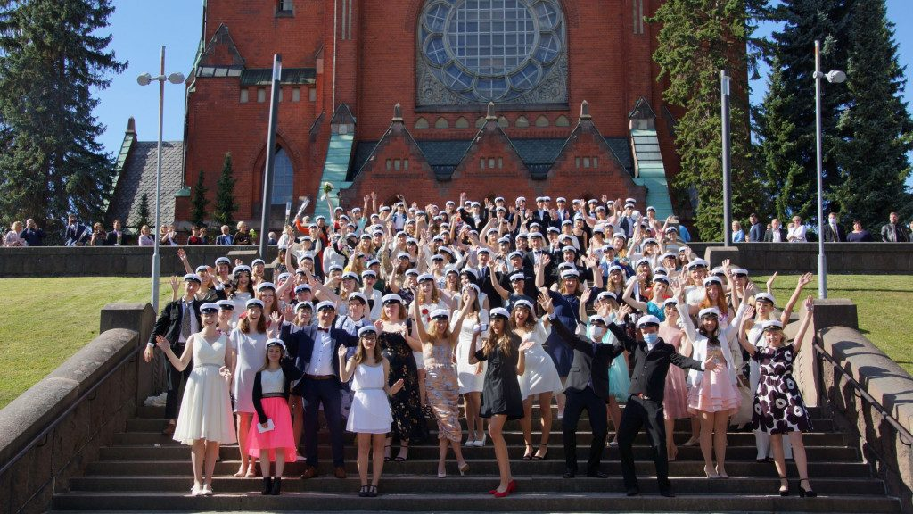 Ylioppilaat tuulettavat ryhmänä kirkon portailla.