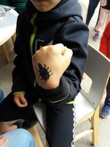 Maalattu hämähäkki kädessä.