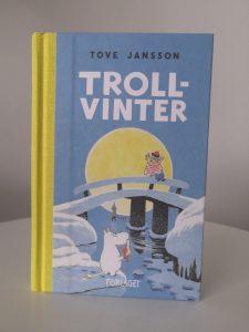 Bild på bokpärmen av Tove Janssons verk Trollvinter, förlagt av Förlaget M. På bilden på pärmen sitter Too-ticki på broräcket och tittar ner mot stranden där Mumintrollet står och håller upp en stormlykta. Månen lyser stort och gult bakom dem. På allra bakerst lyser badhusets ljus på havsstranden.