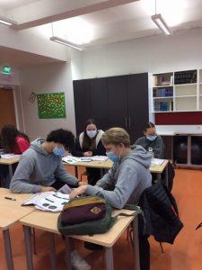 Lukio-opiskelijat tekevät ryhmätyötä kestävästä kehityksestä.