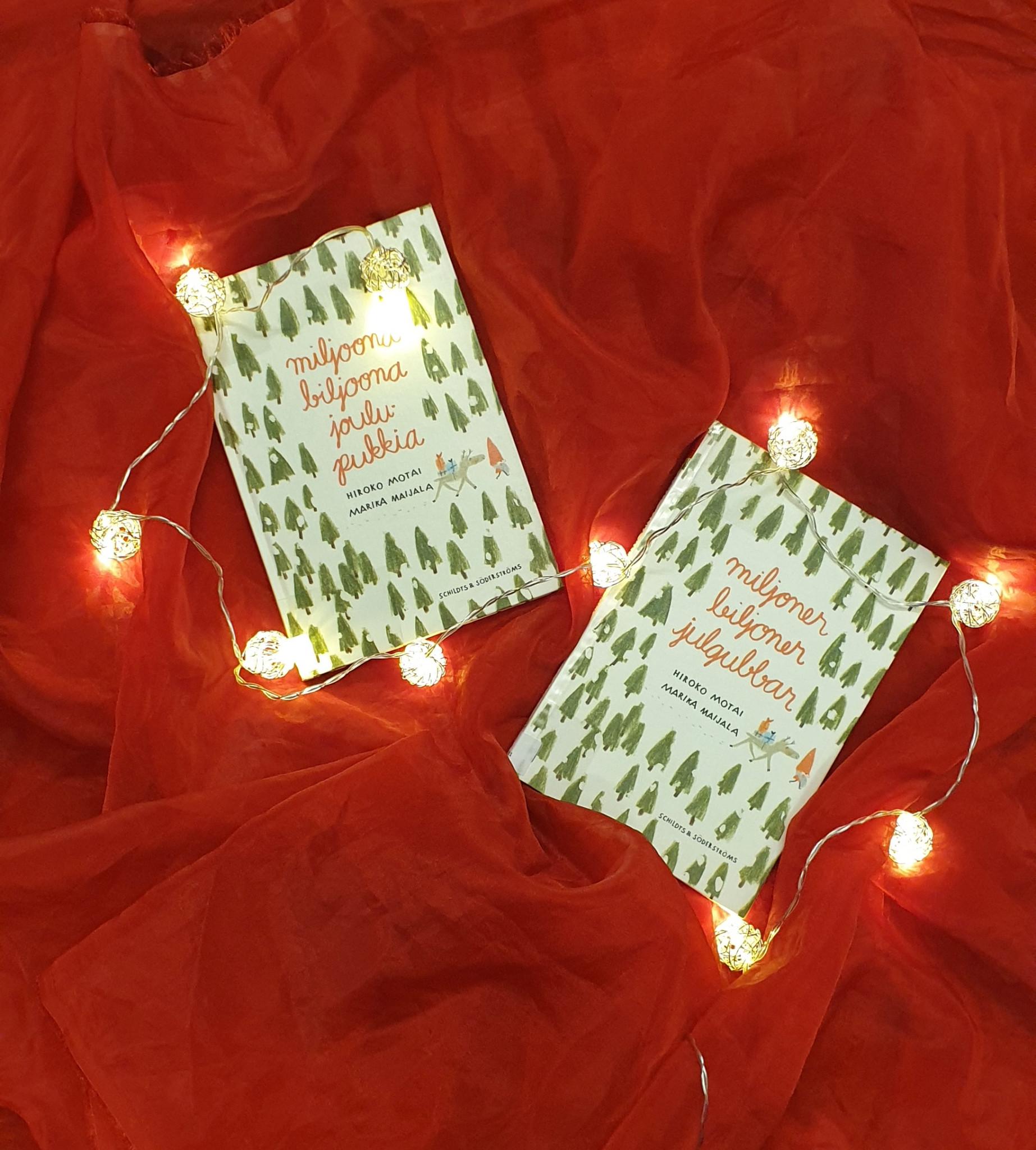 """Jouluinen asetelma, jossa kaksi lastenkirjaa, """"Miljoona biljoona joulupukkia"""" sekä """"Miljoner biljoner julgubbar"""", makaavat punaisella kankaalla. Kirjojen ympärillä kiemurtelee jouluvalosarja."""