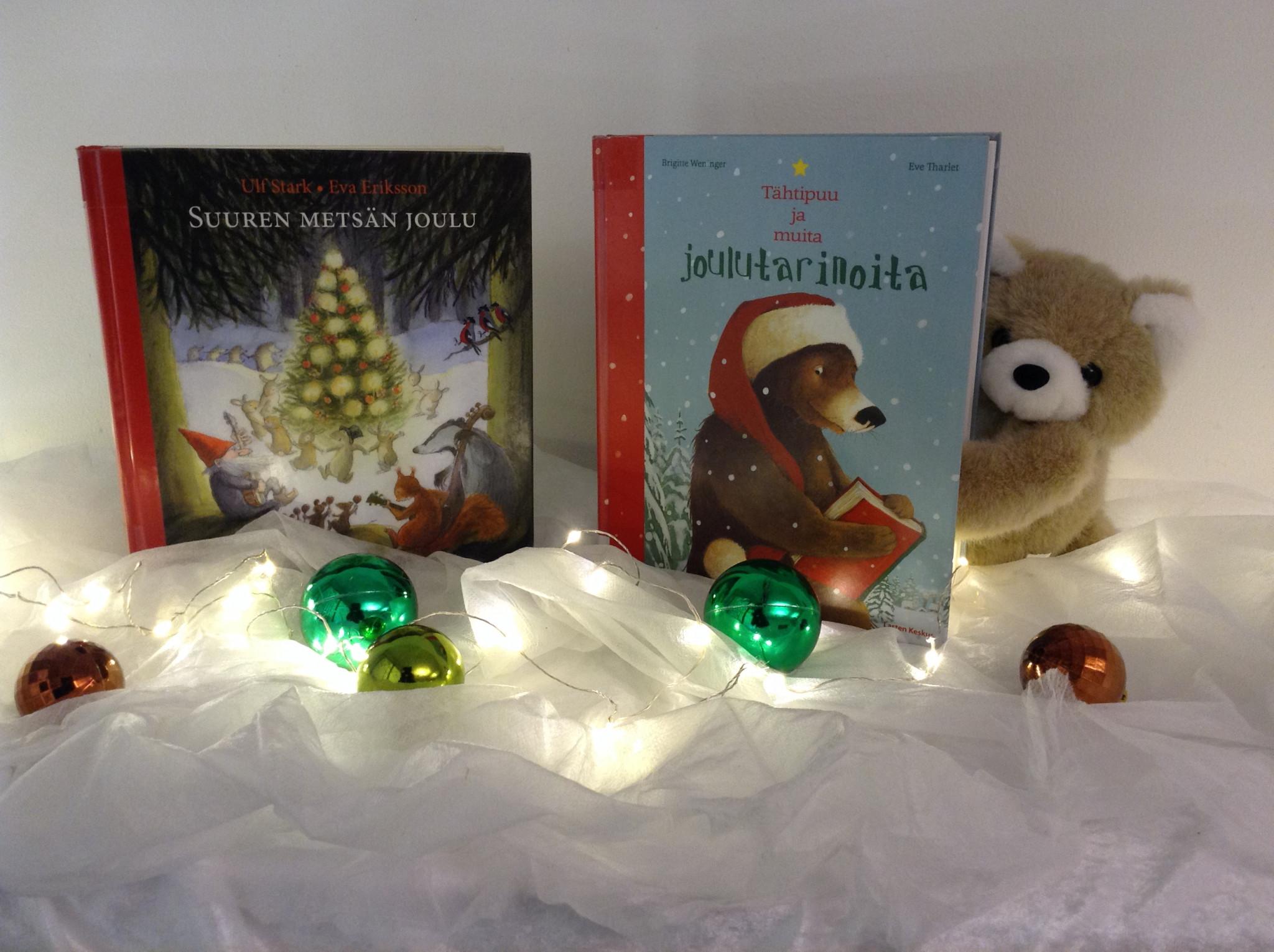 Jouluinen sommitelma, jossa kaksi lasten joulukirjaa nojaa seinään valkoisen, lunta muistuttavan harsokankaan päällä. Toisen takaa kurkkaa nalle. Kirjojen edessä on joulupalloja ja jouluvalosarja.