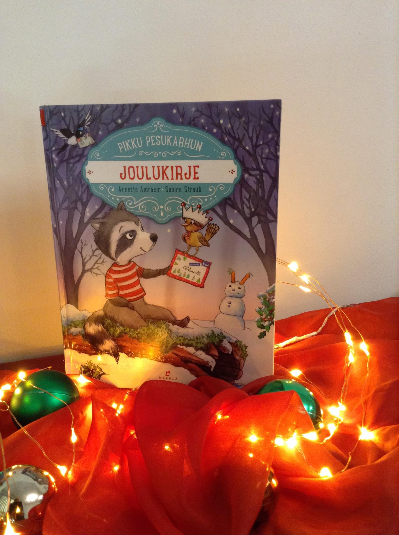 """Jouluinen asetelma, jossa lastenkirja """"Pikku Pesukarhun joulukirje"""" nojaa seinään punaisen kankaan päällä. Kirjan edessä on joulupalloja ja jouluvalosarja."""