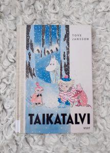 Tove Janssonin kirja Taikatalvi. Kannessa Muumipeikko, Pikkumyy, Tuu-tikki ja Nipsu talvisessa metsämaisemassa..