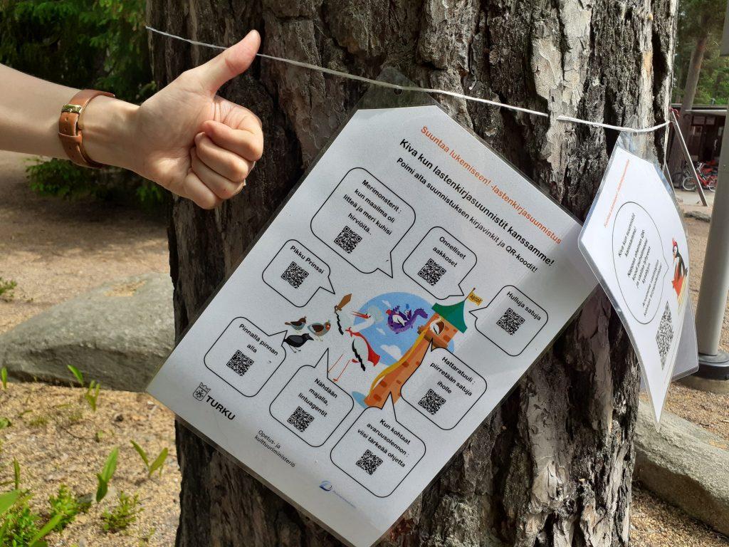"""Puusta roikkuu suunnistusrasti, jossa lukee """"Kiva kun lastenkirjasuunnistit kanssamme!"""". Rastilapun vieressä näkyy kuvan ulkopuolelta tuleva peukuttava käsi."""