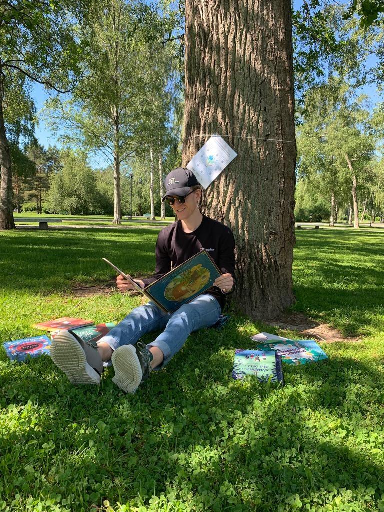 Hymyilevä mies istuu puuta vasten ja lukee lastenkirjaa aurinkoisena päivänä. Hänen ympärillään on useita lastenkirjoja. Puusta hänen takanaan roikkuu suunnistusrasti.
