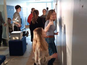 Oppilaita maalaamassa rakennuksia koulun käytävän seinään