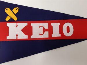 Japanilaisen koulun viiri: sininen, jossa punainen vaakaraita. Raidassa lukee valkoisella KEIO. Viirin vasemmassa yläreunassa on keltaisella kaksi kalligrafiakynää ristissä - Keio Futsubun logo.