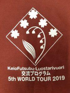 Japanilaisten vaihtoon osallistuville jakaman viininpunaisen pikeepaidan logo: Logossa kieloa ympäröivät sakura-kukat ruudun muotoisessa laatikossa. Laatikon alla on teksti: KeioFutsubu-Luostarivuori, sitten tekstiä japaniksi, sitten 5th WORLD TOUR 2019.