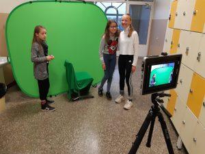 Oppilaita Green Screenin edessä kuvaamassa.
