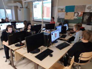 Oppilaita työskentelemässä tietokoneilla ja Micro:biteillä.
