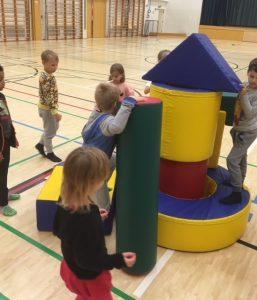 Lapset rakentavat tornia liikuntasalissa