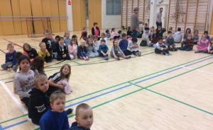 Oppilaat ja eskarilaiset istuvat hevosenkengässä.