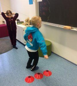 Oppilaat harjoittelevat lukuja hyppien.