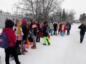 Oppilaat kokoontuneena koulun pihalla.