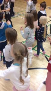 Oppilaat ja eskarilaiset laulavat ja liikkuvat.