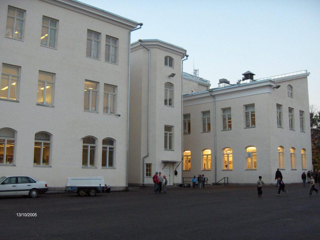 Kuvassa Mikaelin koulurakennus ja välitunnilla leikkiviä lapsia.