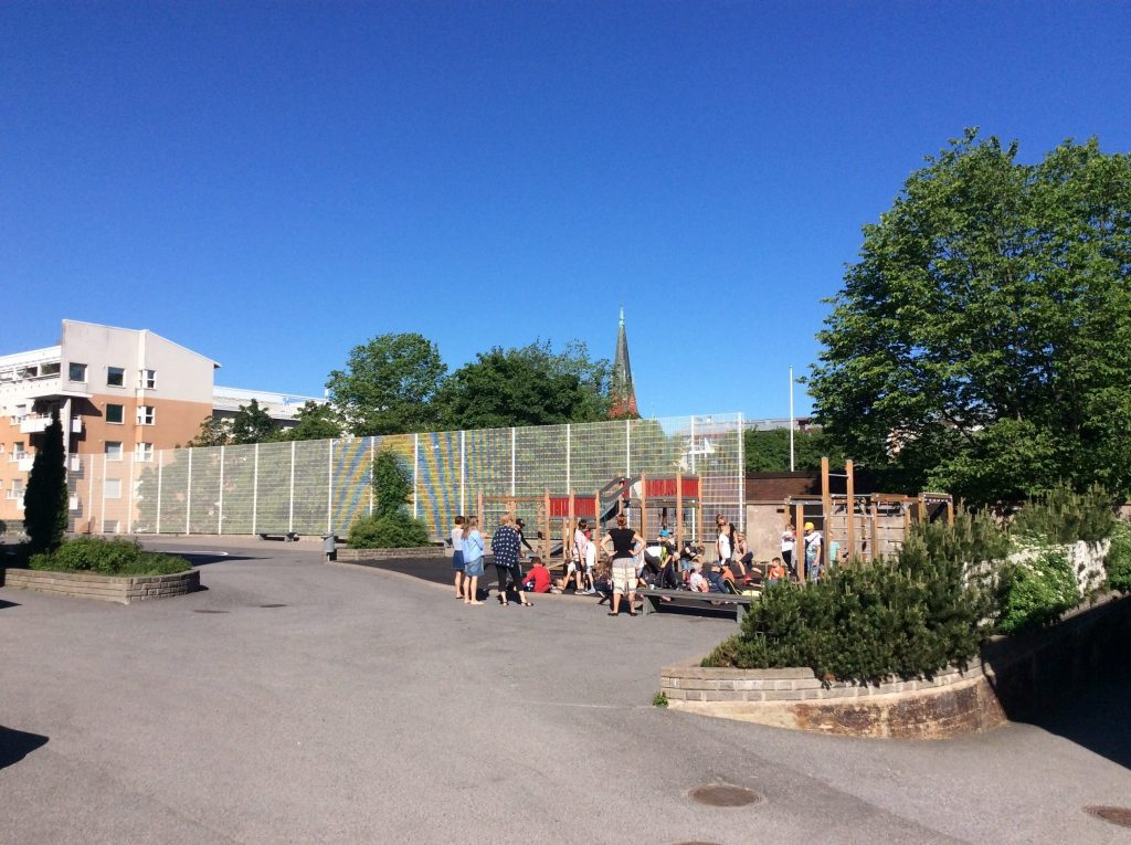 Ensiapukoulutusta oppilaille Mikaelin koulun pihalla. Opettajat valvovat.