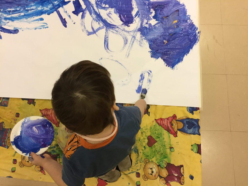 Lapsi maalaa talvimaisemaa.