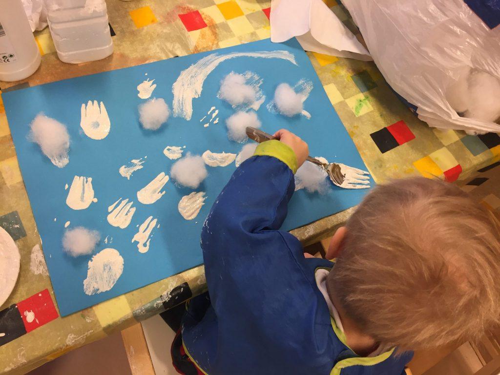Lapsi maalaa talven kukkia haarukalla.