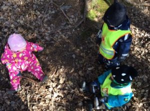 Lapset tutkivat keskittyneesti metsänpohjaa.
