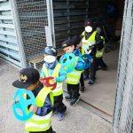 Lapset kulkevat jonossa kädessään pahviset autonratit.