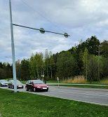 Kolme autoa kulkee autotiellä.