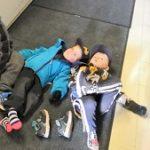 Kaksi lasta makaa väsyneenä lattialla.