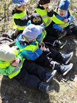 Lapset istuvat maassa ja syövät nauttien suklaamunia.