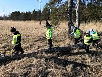 Lapset tasapainoilevat puunrungon päällä.
