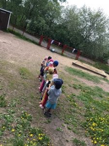Lapset kulkevat jonossa poispäin kuvaajasta.