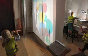 Lapsi katselee kaleidoskoopilla ja sermin takana lapsi tekee piirtoheittimellä muotoja.