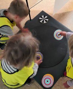 Kolme lasta pyörittää hyrriä alustalla.