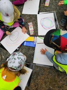 Kolme lasta piirtää valkoiselle paperille taideteoksia värikynillä kallionpäällä metsässä.