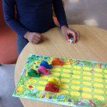 Lapsi pelaa peliä ja on valmiina heittämään noppaa.