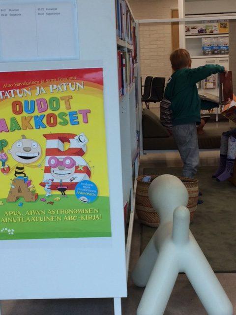 Lapsi näyttää kaverille valitsemaansa kirjaa.